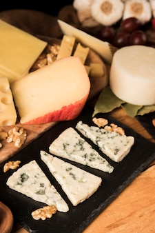 Verity of tasty cheeses and walnut on wooden surface