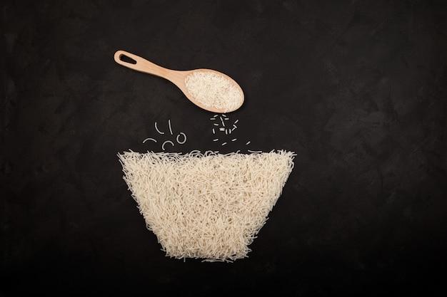 Вермишель или китайская лапша из рисовой муки, выложенная на темном текстурированном фоне в форме миски