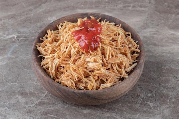 대리석 위에 그릇에 토마토 소스를 곁들인 당면 파스타.