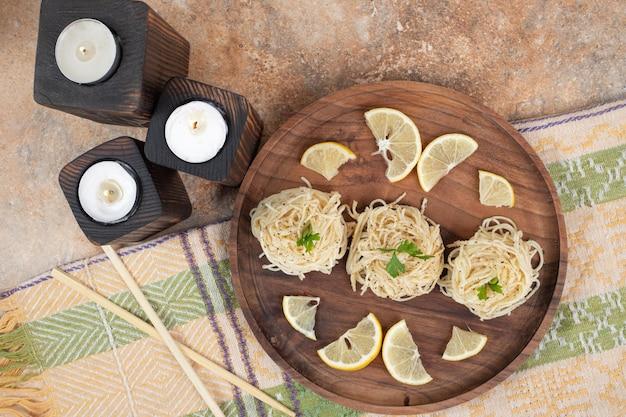 Вермишель с дольками лимона на деревянной тарелке и свечах.
