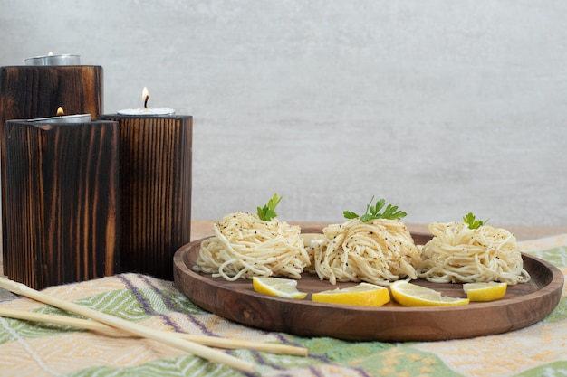 Vermicelli with lemon slices on wooden plate and candles