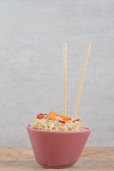 Вермишель со специями и дольками перца на оранжевом фоне. фото высокого качества