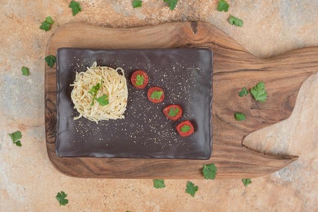 黒いプレートにスパイスとトマトの春雨。高品質のイラスト
