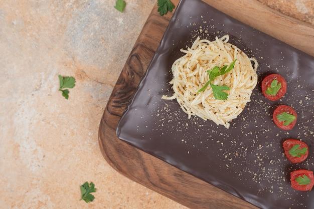 Вермишель со специями и помидорами на черной тарелке. качественная иллюстрация