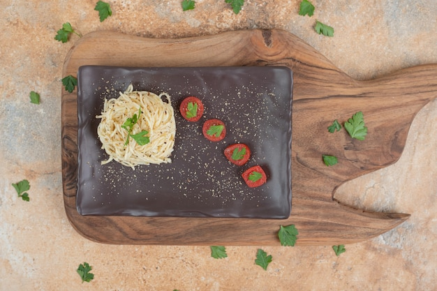 Vermicelli with spices and tomatoes on black plate. high quality illustration