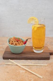 Вермишель с помидорами и стаканом сока на деревянной доске. фото высокого качества