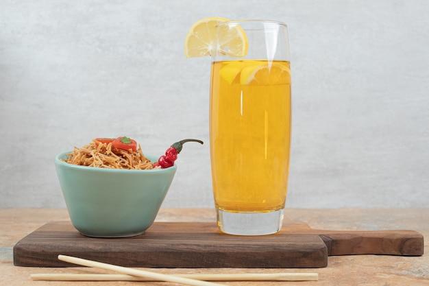 Вермишель с помидорами и стаканом сока на деревянной доске