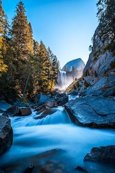 石に落ちる水からヨセミテ国立公園のバーナルフォールズ滝、長時間露光垂直写真。カリフォルニア、米国