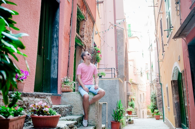 Молодой человек турист в чинкве-терре. молодой кавказский парень гуляя на старую улицу в vernazza