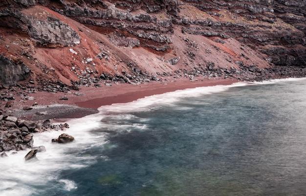 Пляж verodal, пляж с красным вулканическим песком, фотография с большой выдержкой, атлантический океан, эль йерро, канарские острова, испания