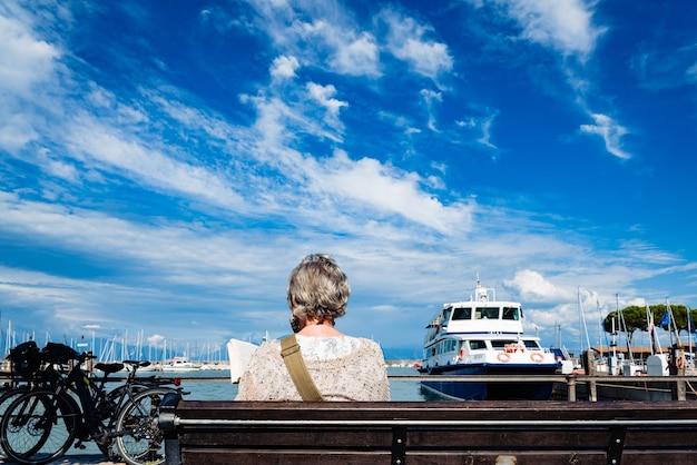 イタリア、ヴェローナ-2021年9月21日:晴れた日に、引退した女性が遊歩道の隣のベンチに座って本を読んでリラックスします。