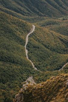 Ripresa aerea verticale di una pericolosa strada di montagna attraverso una foresta di vlasic, bosnia