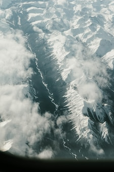 Vertical aerial shot of the mountains covered with snow