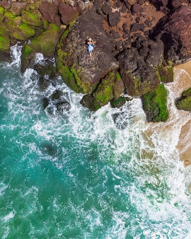 岩のビーチに横たわっている青いドレスを着た女性の垂直空中ショット