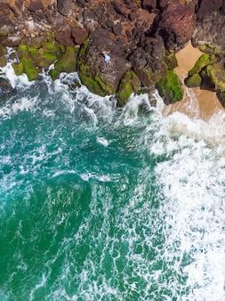 岩の多いビーチに横たわる青いドレスを着た女性の垂直空中ショット