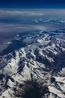 숨막히는 푸른 하늘 아래 눈 덮인 산악 풍경의 수직 공중 총