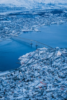 Вертикальный аэрофотоснимок красивого города тромсё, покрытого снегом, сделанный в норвегии.