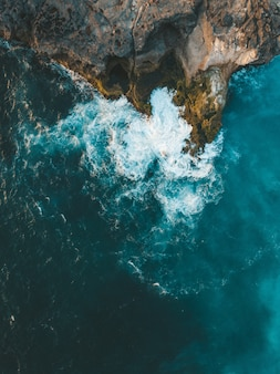 Vertical aerial shot of sea waves hitting the cliff