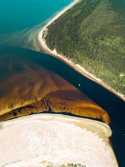 Vertical aerial view of a speedboat sailing along the river on the shore of golden sand