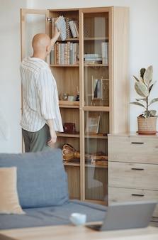 Вертикальный вид сзади на лысого человека, кладущего книгу на полку на деревянный книжный шкаф в современном домашнем интерьере, осознание алопеции и рака, копировальное пространство