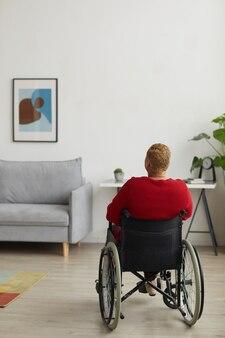 最小限の家のインテリア、コピースペースで車椅子を使用して障害を持つ現代の女性の垂直背面図