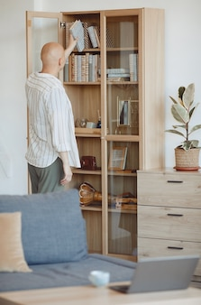 Vertical back view at bald person putting book on shelf on wooden bookcase in modern home interior, alopecia and cancer awareness, copy space