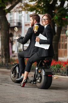 Вертикальное изображение заднего вида счастливой элегантной пары едет