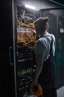 Vertical back view of network engineer in server room during maintenance work in data center