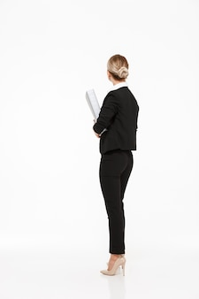 白い壁に大きなフォルダーを保持している金髪のビジネス女性の垂直背面図