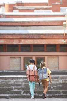 Vertical back view portrait of two sisters going to school with backpacks while walking up stairs to big building, copy space