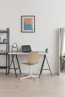Вертикальный фон фон минимального домашнего офиса на рабочем месте в современной квартире, украшенной абстрактным искусством, копией пространства