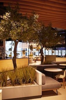 生きている木、コピースペースで飾られたモダンなショッピングモールの空のフードコートのインテリアの垂直背景画像