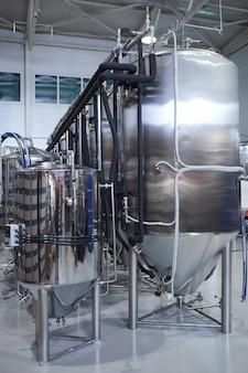 Вертикальное фоновое изображение резервуаров для фильтрации и ферментации на современном промышленном пивоваренном заводе, копией пространства