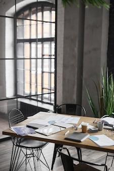 Вертикальное фоновое изображение деревянного стола с документами, разбросанными после деловой встречи в офисе, копией пространства