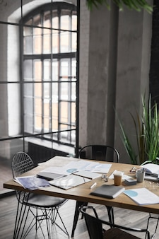 Vertical background image of wooden table with documents scattered on after business meeting in office, copy space
