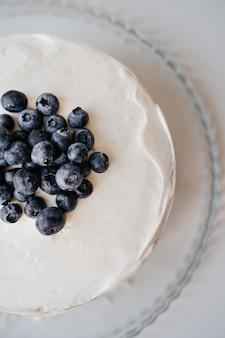 白い木製のキッチンテーブルの上のブルーベリーチーズケーキの垂直背景。白いバタークリームに大きなベリー。