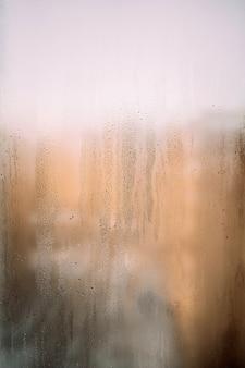 雨の後の太陽と滴の濡れた窓の垂直背景テクスチャ暖かい写真高品質