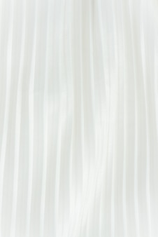 Vertical background of white pleated fabric located vertical. elegance female summer skit.