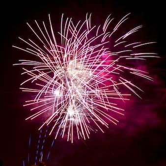 Bello scatto verticale di fuochi d'artificio colorati sotto il cielo notturno