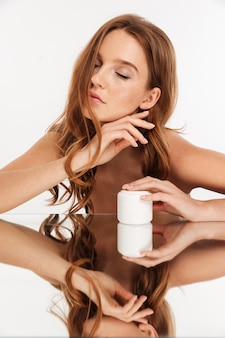 Vertical beauty portrait of ginger woman with long hair and closed eye sitting by the mirror table with body cream