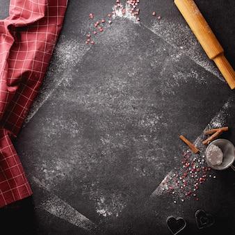 밀가루와 가루 설탕을 뿌린 세로 검정색 배경과 주방 용품