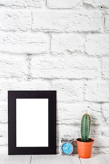 Vertical black cardboard photo frame on white table. mockup