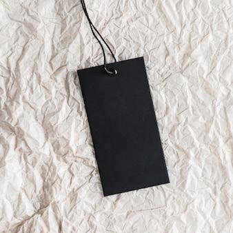 Вертикальная черная бирка для одежды на белой бумаге как экологически чистый органический материал на фоне экологичного ф ...