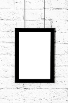 Vertical black photo frame hanging on brick wall. mockup with copy space.