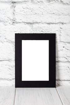 Vertical black photo frame on wooden table. mockup with copy space