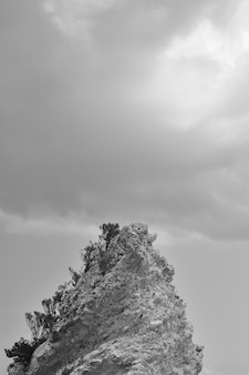 Vertical black and white shot of a rocky formation with clouds