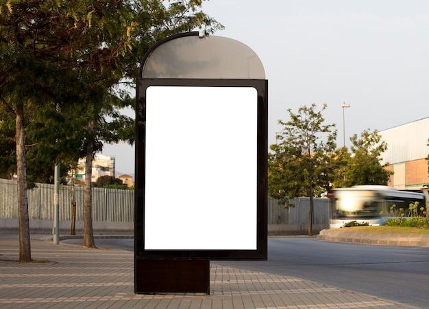 Вертикальный пустой рекламный щит на городской улице с зелеными деревьями и движением автобуса