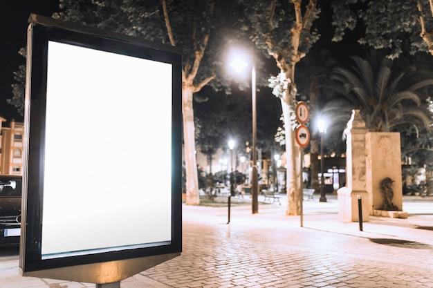 Vertical blank billboard on street at night