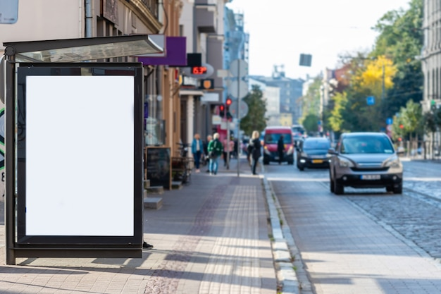 Vertical blank white billboard at bus stop on city street, mock-up