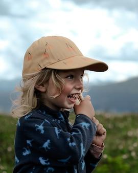 Ragazza bionda verticale che indossa un berretto marrone